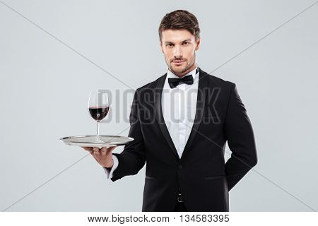 Portrait of young waiter in tuxedo holding glass of red wine on silver tray