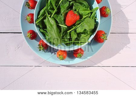 Fresh spinach salad with spinach and strawberries on wooden light pink table