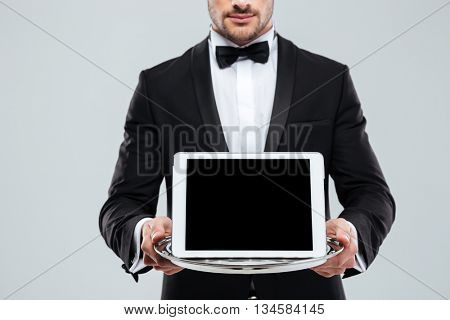 Closeup of blank screen tablet on tray holded by waiter in tuxedo with bow tie