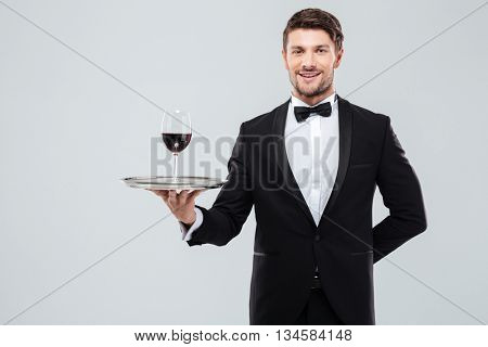 Cheerful young waiter in tuxedo standing and holding glass of red wine on tray