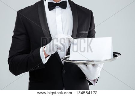 Closeup of butler in tuxedo and gloves holding blank card on tray