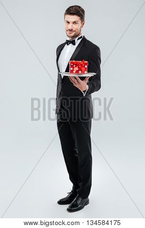 Full length of young butler in tuxedo standing and holding tray with gift box