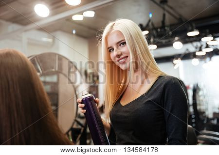 Close-up portrait of a hairdresser with hair spray fixating client hairdo at salon