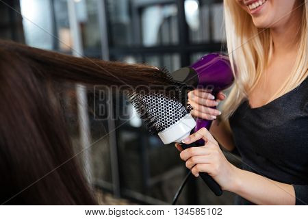 Close-up portrait of a young female stylist drying woman hair in beauty salon