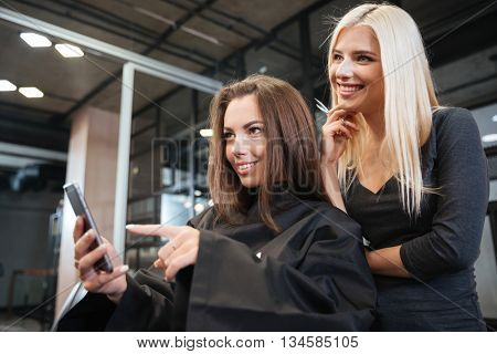 Happy young woman pointing at smartphone and hairdresser making hair styling at salon