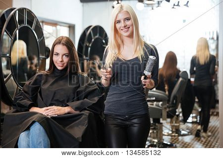 Beautiful young blonde female hairdresser holding scissors and comb looking at camera