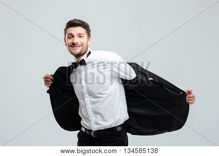 Cheerful young man in tuxedo standing and taking off his jacket