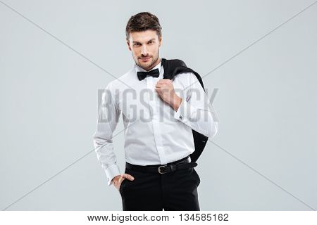 Gorgeous young man in tuxedo standing and holding his jacket