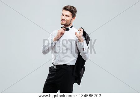 Attractive young man in tuxedo holding his jacket