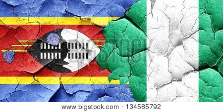 Swaziland flag with Nigeria flag on a grunge cracked wall