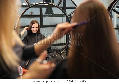 Mirror reflection of young woman getting her hairdo by stylist at parlor
