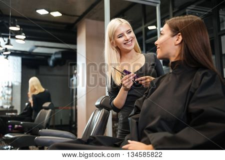 Woman hair stylist making hairdo to attractive young girl with sitting in beauty salon