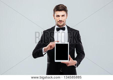 Confident young man in tuxedo standing and holding blank screen tablet