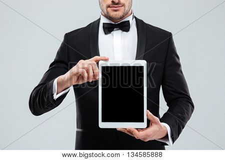 Closeup of handsome young man in tuxedo with bowtie holding blank screen tablet
