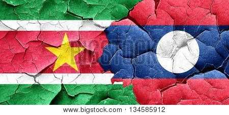 Suriname flag with Laos flag on a grunge cracked wall