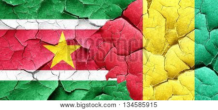 Suriname flag with Guinea flag on a grunge cracked wall