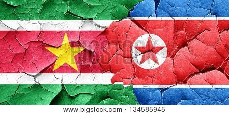 Suriname flag with North Korea flag on a grunge cracked wall