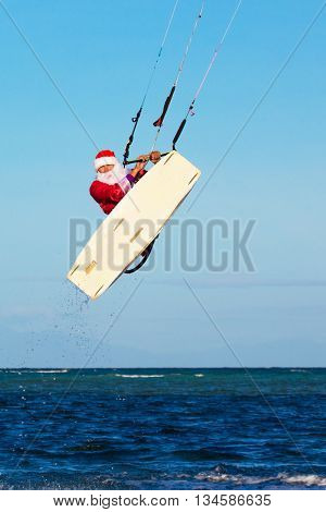 young man on the kite in the costume of Santa Claus. Christmas and New year on a tropical island. Extreme Sport Kitesurfing