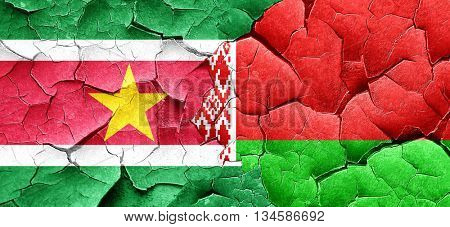 Suriname flag with Belarus flag on a grunge cracked wall