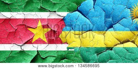 Suriname flag with rwanda flag on a grunge cracked wall