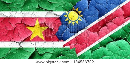 Suriname flag with Namibia flag on a grunge cracked wall