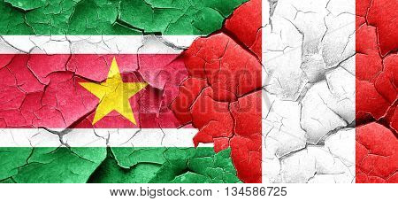 Suriname flag with Peru flag on a grunge cracked wall