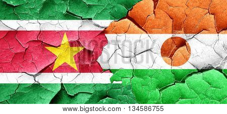 Suriname flag with Niger flag on a grunge cracked wall