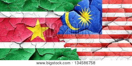 Suriname flag with Malaysia flag on a grunge cracked wall