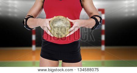 Female athlete with elbow pad holding handball against digital image of handball goal
