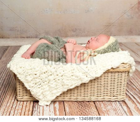 beautiful sleepy swaddled newborn baby in knitted hat