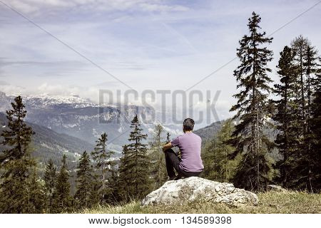 Hiker sitting on rock on a mountain top in beautiful alpine landscape. Active lifestyle natural environment meditation serenity and sports concept. Dramatic sky in the background.