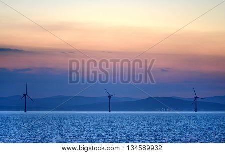 Offshore wind turbines at sunset off the Irish coast