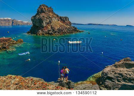 Tourists on the Armeni bay beach near Oia village at Santorini island in Aegean sea, Greece