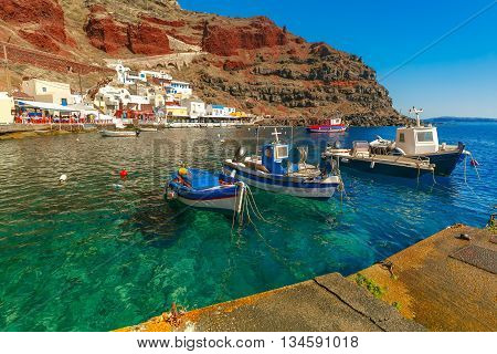 Fishing boats at Old port Ammoudi of Oia village at Santorini island in Aegean sea, Greece