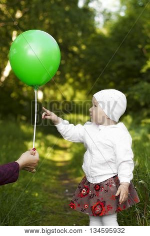 little girl curiously shows a balloon in summer on nature