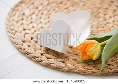 A fresh spring orange tulip and two cute heart symbols on the straw board. Home romantic