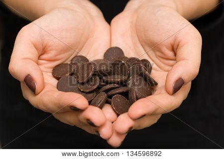 Young woman's hands in a shape of heart with dark chocolate. Enjoy healthy lifestyle. Chocolate chips for home baking and cacao. Happy days at home.