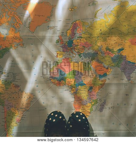 Beautiful concept for summer travel. Small children's shoes on the world map. Planning a summer vacation and holidays.