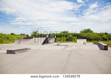 Skatepark with a Halfpipe and Ramps with blue sky and clouds.