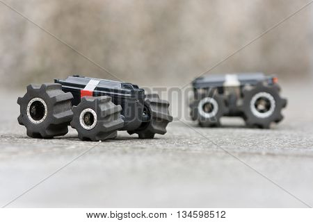 Two toy cars on a ground ready for a test-drive. Activities and games with children outdoors. miniature vehicles on remote control
