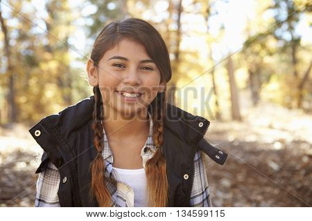 Head and shoulders portrait of a Hispanic girl in a forest