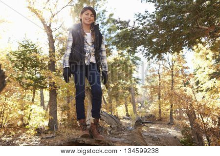 Hispanic girl on fallen tree in a forest looking to camera