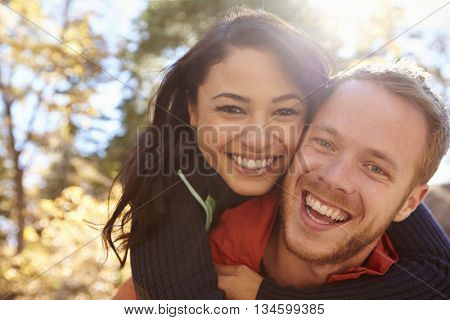 Backlit portrait of mixed race couple embracing in a forest