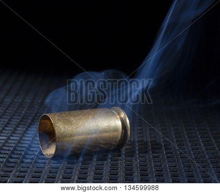 Empty handgun brass with smoke on a black grate