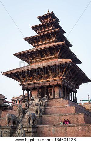 Bhaktapur, Nepal - December 4, 2014: People sitting on steps of Nyatapola Pagoda on Taumadhi Sqaura.