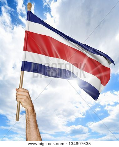 Person's hand holding the Costa Rican national flag and waving it in the sky, part 3D rendering