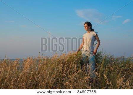 Happy woman stands in the prairie among the tall grass on the background of the blue sky looking into the distance and smiling. Sunset in the prairie.