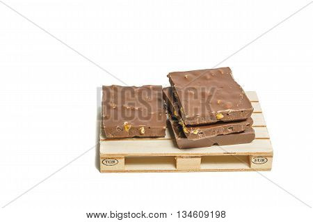 Heap of broken chocolate pieces on wooden pallet and white background