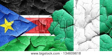 south sudan flag with Nigeria flag on a grunge cracked wall