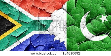 South africa flag with Pakistan flag on a grunge cracked wall